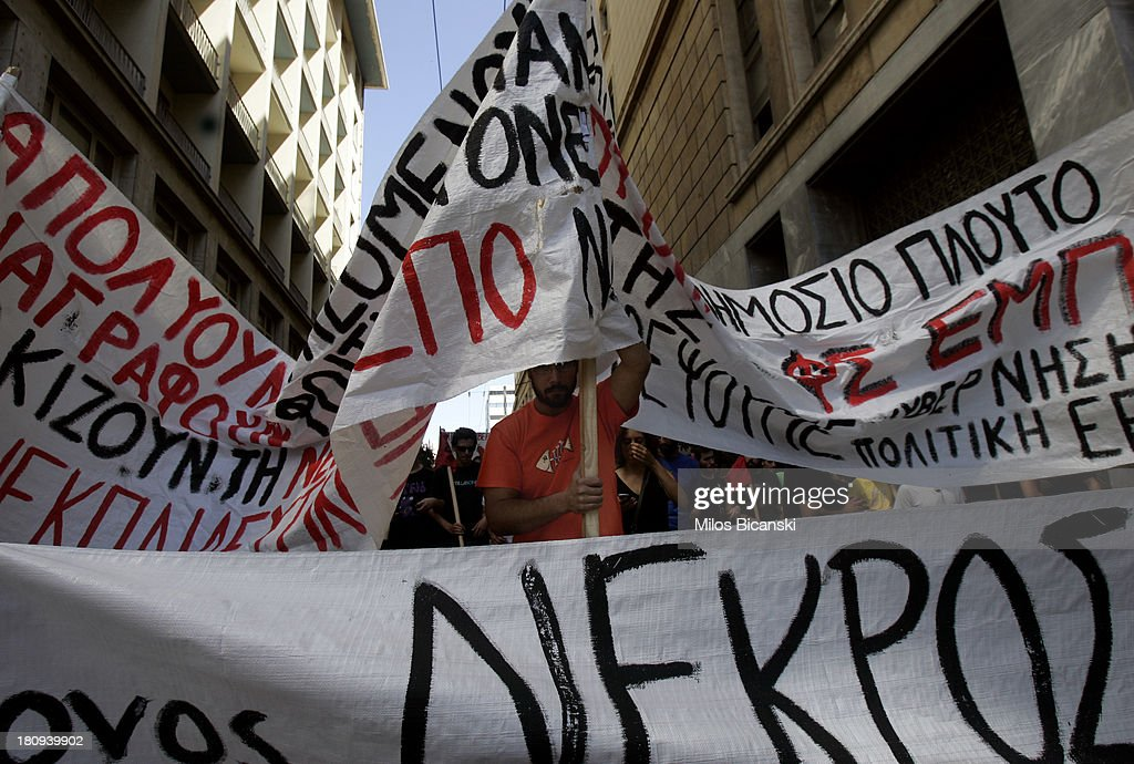 Civil servant protest with banners during a demonstration against austerity and job cuts on September 18, 2013 in Athens, Greece. As part of the redeployment plan in the country reeling from six years of recession, civil servants have to accept new posts or spend eight months on reduced salaries as alternative posts are found, with the risk of losing their jobs altogether.