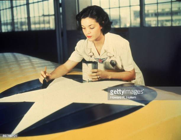 Civil Service employee Irma Lee McElroy paints insignia on airplane wings at the Naval Air Station Corpus Christi Texas August 1942