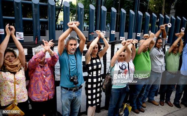 Civil society activists and journalists pretend to turn themselves in during a protest against alleged government spying on the media and human...
