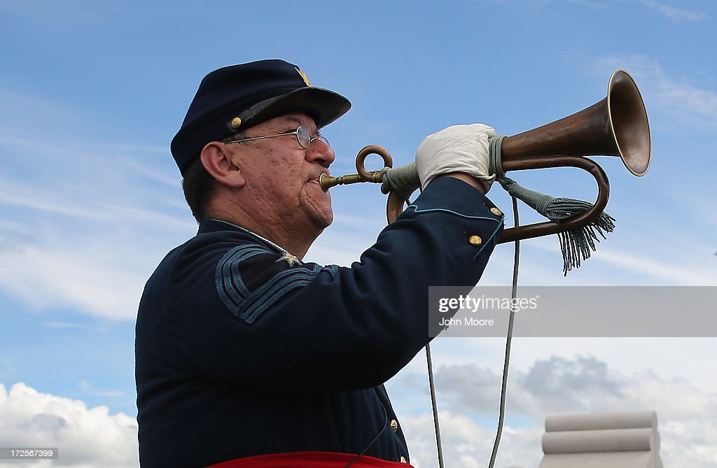 Civil War reenactor raises his bugle before playing 'Taps' after a reenactment of Pickett's Charge on the 150th anniversary of the historic Battle of...