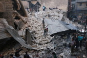 Civilans and rescue teams inspect the rubble of a destroyed building following a reported air strike by Syrian government forces on the Kallassa...