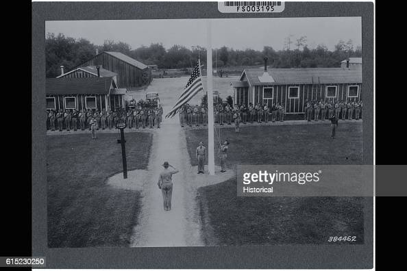 Civilian Conservation Corps personnel at a CCC retreat stand at attention saluting the American flag as it is raised over the grounds of their camp...