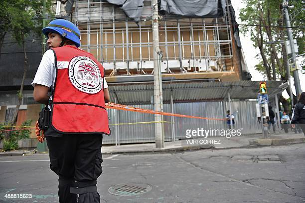 Civilian Protection members close an area where firefighters work to demolish a damaged wall after a strong earthquake in Mexico City on May 8 2014 A...