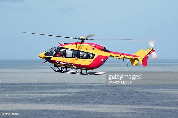 A Civilian Security EC145 helicopter flies over the Bay of Mont SaintMichel in Normandy on May 5 2015 during a large air evacuation drill in order to...