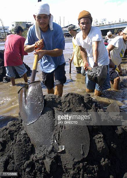 Civilian volunteers use hand spades to dig beside a riverbank 03 December 2006 near Legaspi City to try to locate bodies of people believed to have...