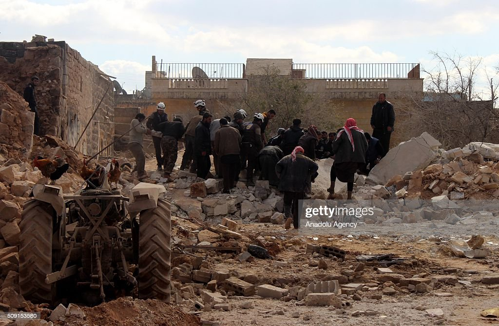 Civilians and rescue workers inspect collapsed buildings after Russian Forces' airstrike over opposition controlled residential areas in Idlib's Talmanes Town, Syria on February 09, 2016.