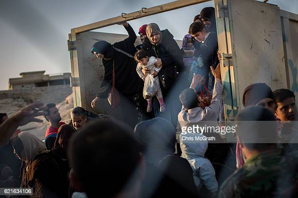 Civilians are assisted as they arrive by truck at the entrance of the Hasan Sham IDP camp after fleeing fighting in Mosul on November 7 2016 in...