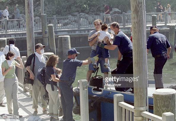 Civilians are evacuated by boat near the site of the collapse of the World Trade Center on September 11 2001