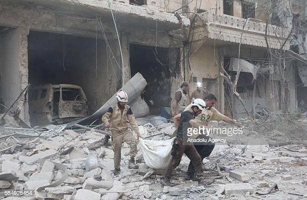 Civilians carry a dead body after Assad forces hit residential areas in Ansari neighborhood of Aleppo Syria on July 31 2016 Several casualties...