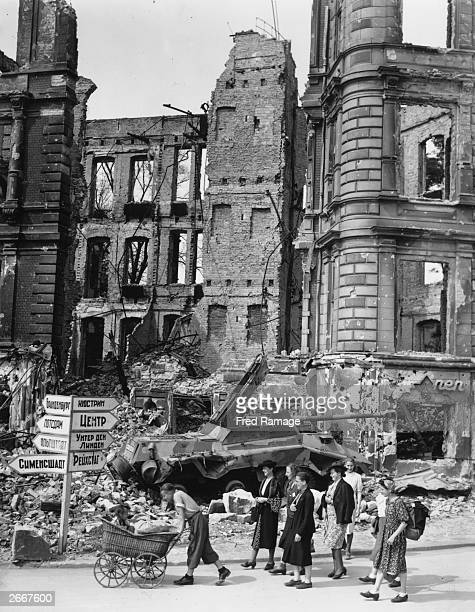 Civilians carrying their bundled belongings walk passed Russian street sign in the Mollendorf Platz in conquered Berlin In the ruins there lies the...