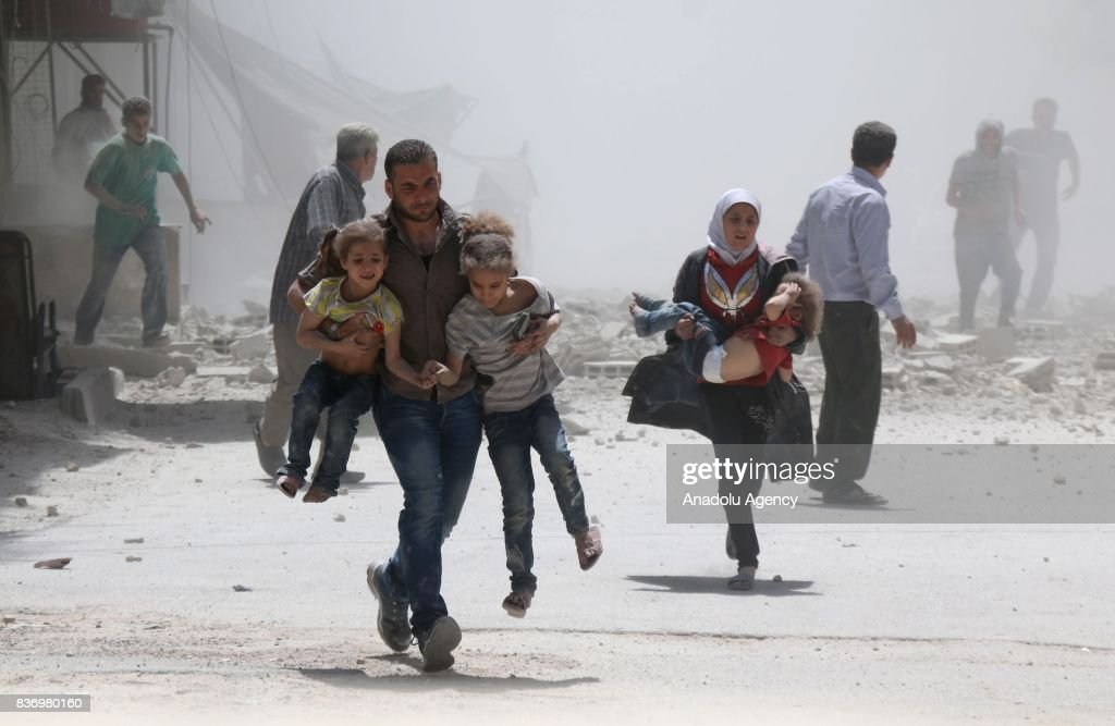Civilians escape from explosion site after Assad Regime's forces strike over the de-conflict zone, Ein Tarma Town of Eastern Ghouta region of Damascus, Syria on August 22, 2017.