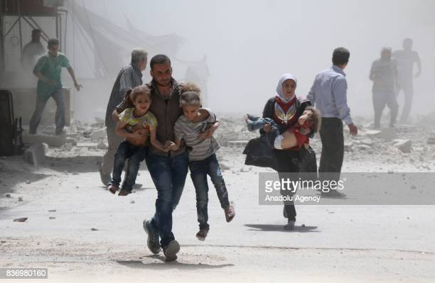 Civilians escape from explosion site after Assad Regime's forces strike over the deconflict zone Ein Tarma Town of Eastern Ghouta region of Damascus...