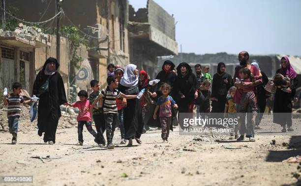 TOPSHOT Civilians flee from the Old City of Mosul as Iraqi forces advance on June 20 during the ongoing offensive by Iraqi forces to retake the last...
