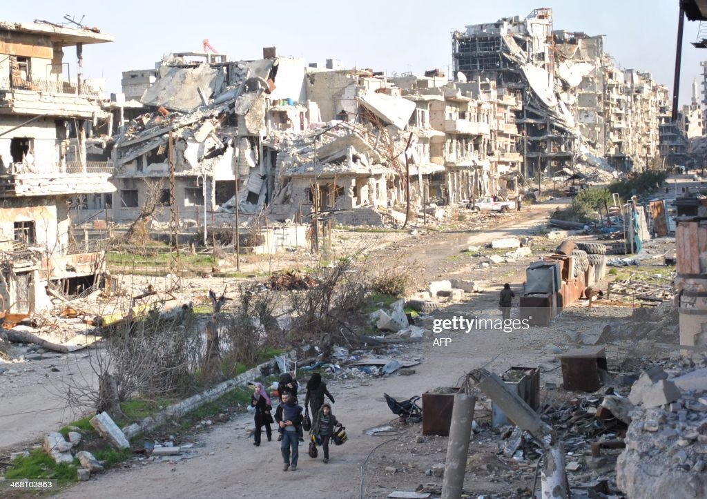Civilians leave the the besieged district of the central Syrian city of Homs ahead of being evacuated by United Nations staff to a safer location on...