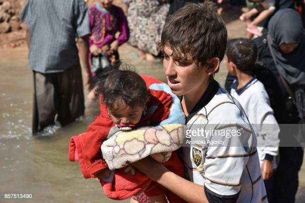 Civilians make their way through endangered areas filled with mines and bomb traps to get to safety in Peshmerga controlled areas in Kirkuk Iraq on...