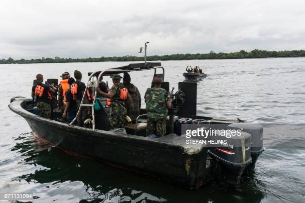 Civilians raise their hands as they approach members of the NNS Pathfinder of the Nigerian Navy forces on April 19 2017 in the Niger Delta region...