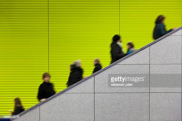 Civilians riding an escalator with a green screen background