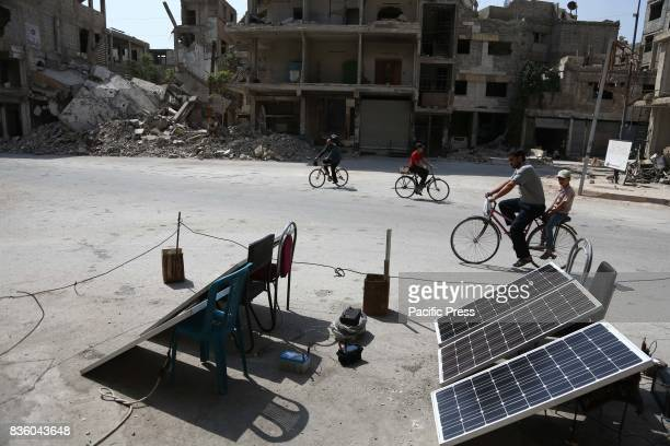 Civilians riding bicycles passed a number of solar panels One of the people is charging the batteries to the people in Zamalka in the eastren ghouta...