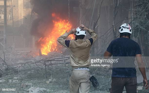 Civilians try to rescue people as the fire fighters extinguish the fire after Assad forces hit residential areas in Ansari neighborhood of Aleppo...