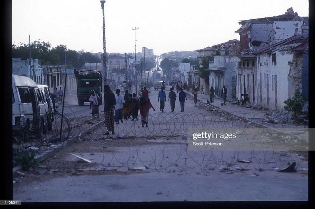 Civilians walk along a destroyed street May 4 1993 in Mogadishu Somalia Following the departure of US forces UN troops continue the humanitarian...