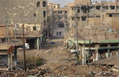 Civilians walk near rubble January 30 2007 in the center of Ramadi in Iraq's Anbar province The area has seen some of the heaviest fighting between...