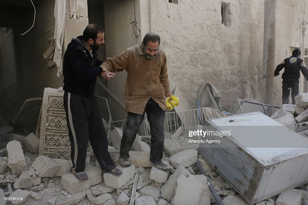 Civilians walk past the rubbles of damaged buildings after the Russian airstrikes targeted residential areas in opposition controlled Katranci neighborhood of Aleppo, Syria on February 14, 2016.