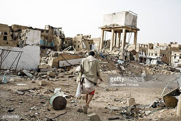 Civilians walk through the destroyed city of Sadah Yemen on June 15 2015 The Arab coalition has been carrying out air strikes on a daily basis in...