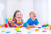 Kids playing with wooden toys. Two children, cute toddler girl and funny baby boy, playing with wooden toy blocks, building towers at home or day care. Educational child toys for preschool and kinderg