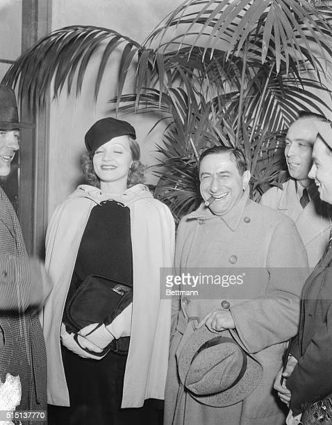 Clad in a leather skirt and cape Marlene Dietrich is shown as she was greeted by director Ernst Lubitsch on her arrival back in Hollywood after her...