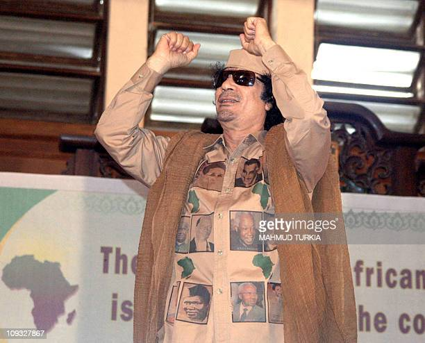 Clad in an outfit featuring Independence African of States legends Libyan leader Moamer Kadhafi waves to wellwishers as he arrives in the capital...