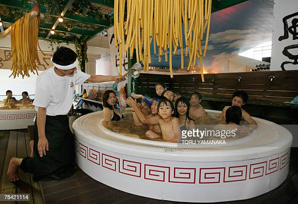 Clad in chef costume an employee of Hakone Kowakien Yunessun put noodleshaped bath articles into a 2meter wide bathtub modeled Chinese noodle bowl in...