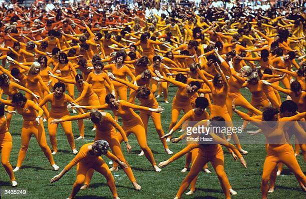Clad in orange leotards and tights women of all ages and abilities give a display of eurhythmics at a gymnastic festival in Stuttgart In Germany book
