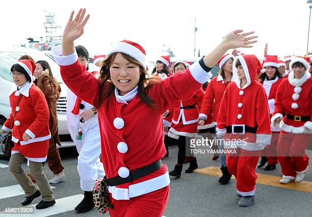 Clad in Santa Claus costumes volunteers wave to salespersons at a seafood shopping center which was damaged by the earthquake and tsunami on March 11...