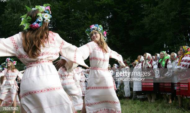 Clad in Ukrainian traditional outfit Ukrainian girls dance as elderly women look on at Pirogovo village near Kiev during a celebration of Ivana...