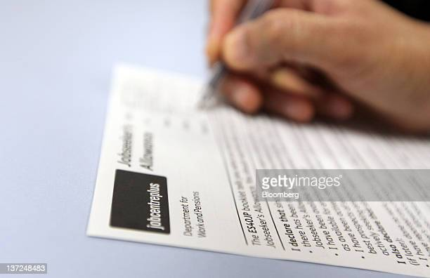 A claimant fills in a job seekers allowance form at a job centre in London UK on Tuesday Jan 17 2012 Britain faces the 'toughest' job market in two...