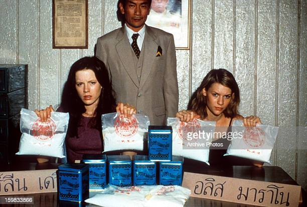 Claire Danes and Kate Beckinsale holding up bags of white substance in a scene from the film 'Brokedown Palace' 1999