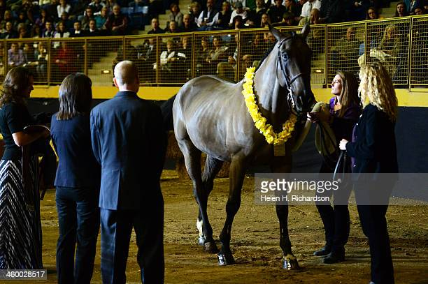 Claire Davis' horse trainer Rebecca Johnson far right holds the reins of Claire's horse Graphite as her parents Desiree and Michael Davis left get...