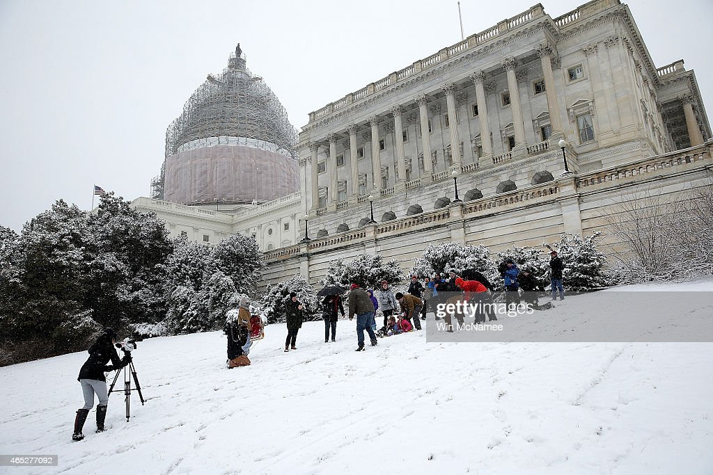 Claire McKeon and Megan Krepp are interviewed while sledding on the west lawn of the US Capitol during a snow storm March 5 2015 in Washington DC...