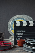 Clapperboard, tin boxes with film and lens stand on a wooden table.