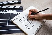 hand with holding pencil for writing  storyboard in sketchbook beside clapperboard