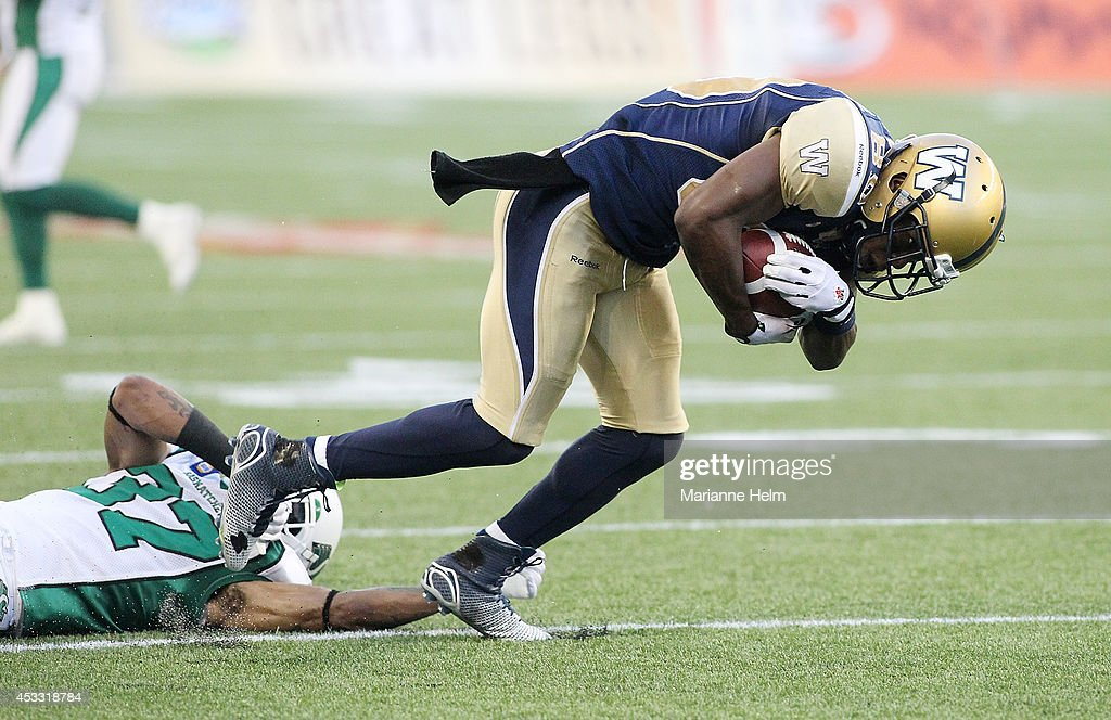 Clarence Denmark #89 of the Winnipeg Blue Bombers breaks free from the grasp of Rod Williams #37 of the Saskatchewan Roughriders in first half action in a CFL game at Investors Group Field on August 7, 2014 in Winnipeg, Manitoba, Canada.