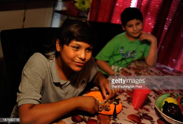 Clarissa Munoz and her brother Antonio Salas eat some chicken and mashed potatoes made by their mother Blanca Salas for dinner in their home in...