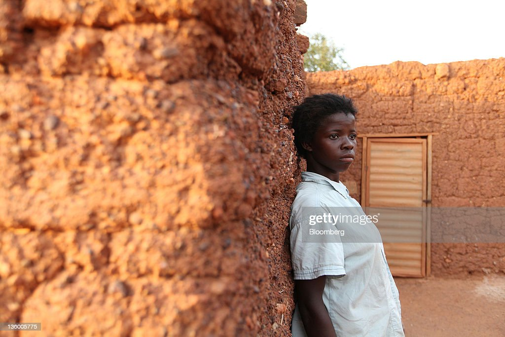 Clarisse Kambire, 13, a child laborer, poses for a photograph outside the hut where she sleeps and which she shares with her foster parent Victorien Kamboule in Benvar, Burkina Faso, on Friday, Nov. 11, 2011. In Burkina Faso, one of the poorest countries in the world, where child labor is endemic to the production of its chief crop export, paying lucrative premiums for organic and fair traden cotton has -- perversely -- created fresh incentives for exploitation. Photographer: Chris Ratcliffe/Bloomberg via Getty Images