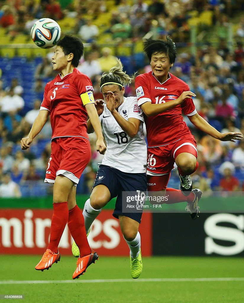 Clarisse Le Bihan (C) of France jumps for a header with Choe Sol Gyong (L) and Ri Un Yong of Korea DPR during the FIFA U-20 Women's World Cup Canada 2014 3rd place match between Korea DPR and France at Olympic Stadium on August 24, 2014 in Montreal, Canada.