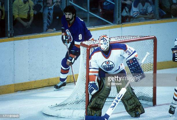 Clark Gillies of the New York Islanders skates behind the net as goalie Grant Fuhr of the Edmonton Oilers looks on during the 1984 Stanley Cup Finals...