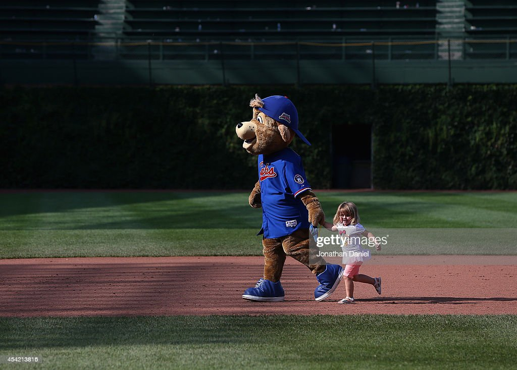 'Clark' the macot of the Chicago Cubs, runs the bases with a small child after a game against the Baltimore Orioles at Wrigley Field on August 24, 2014 in Chicago, Illinois. The Cubs defeated the Orioles 2-1.