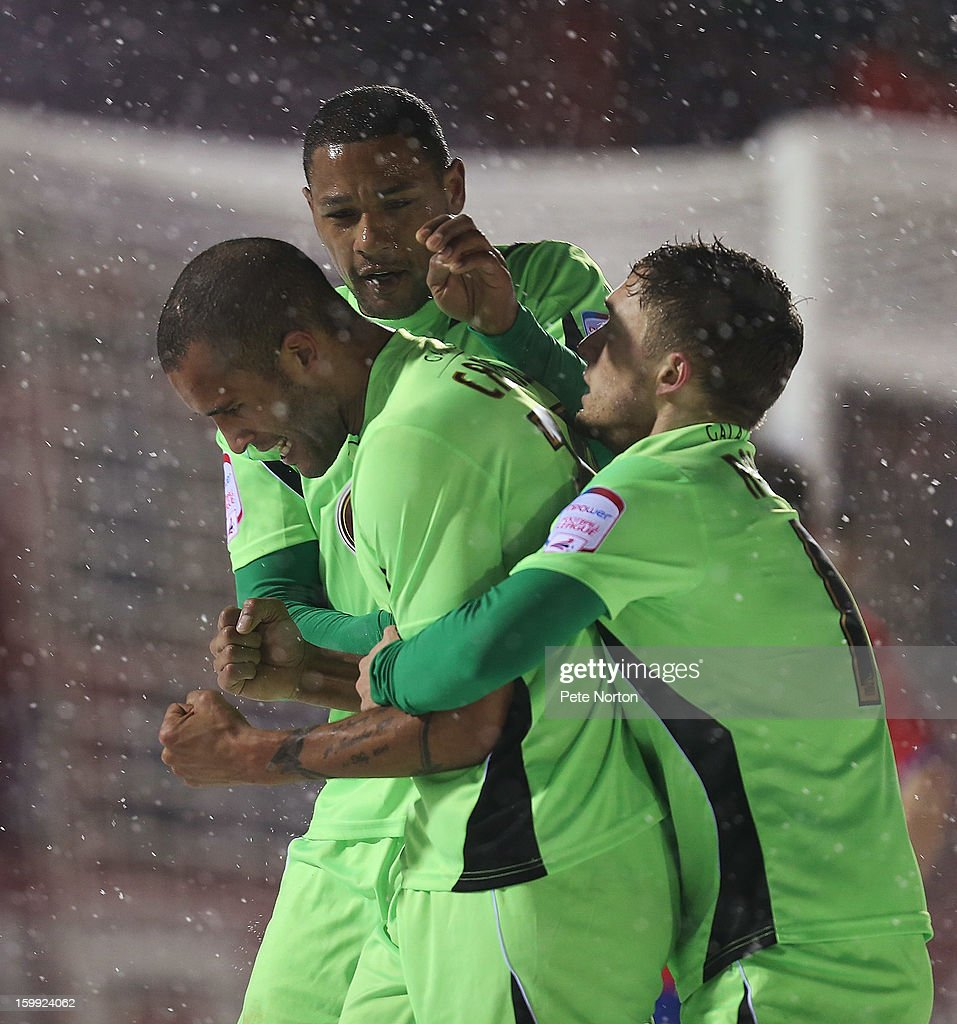 Clarke Carlisle of Northampton Town is congratulated by team mates Clive Platt and Jake Robinson after scoring his sides 2nd goal during the npower League Two match between Aldershot Town and Northampton Town at the EBB Stadium on January 22, 2013 in Aldershot, England.