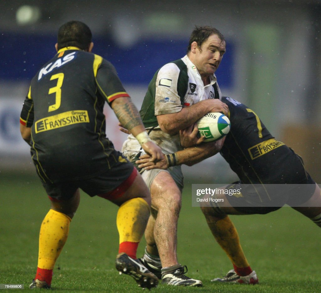 Clarke Dermody of London Irish is tackled by Dominic Chouly during the Heineken Cup match between Perpignan and London Irish at Stade Aime Giral on...