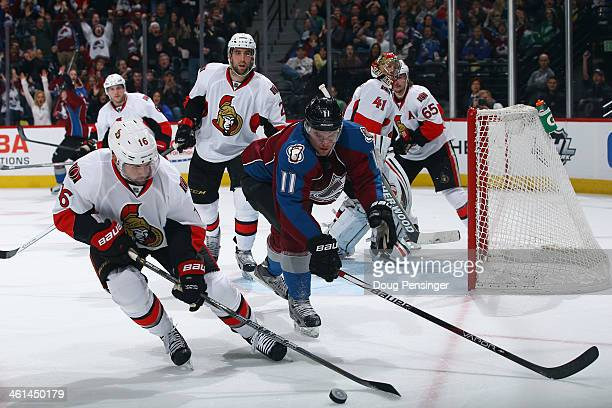 Clarke MacArthur of the Ottawa Senators and Jamie McGinn of the Colorado Avalanche vie for control of the puck at Pepsi Center on January 8 2014 in...