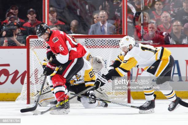 Clarke MacArthur of the Ottawa Senators battles for the loose puck against Nick Bonino of the Pittsburgh Penguins in Game Three of the Eastern...